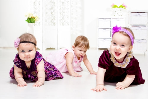 three cute toddlers crawling