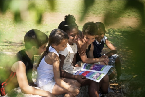 a group of children watching on a colorful page of a book