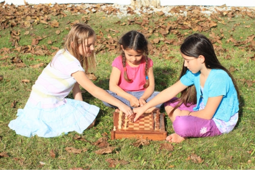 three little girls playing chess outdoor